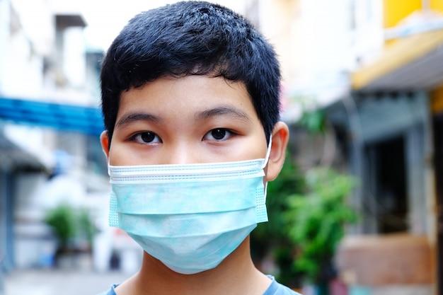 細菌、有毒ガス、埃を防ぐためにマスクを身に着けている若いアジアの少年。細菌感染の防止コロナウイルスまたはcovid 19。
