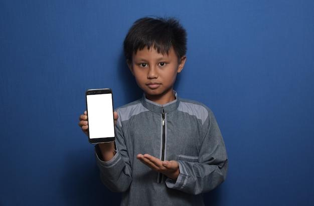 카메라를 보고 빈 흰색 스마트폰 화면을 보여주는 이슬람 옷을 입고 젊은 아시아 소년
