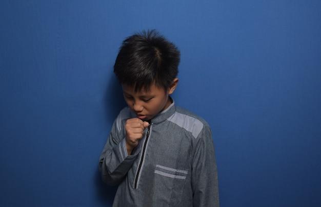 이슬람 드레스를 입은 젊은 아시아 소년은 감기나 기관지염의 증상으로 몸이 좋지 않고 기침을 한다