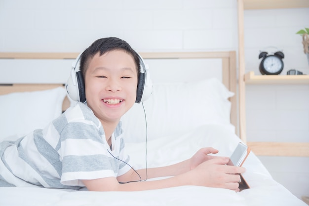 Young asian boy wearing headset while using tablet computer in bedroom