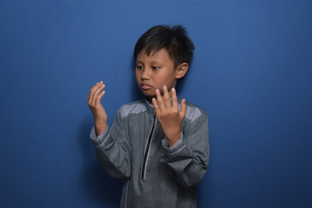 Young asian boy wearing muslim clothes praying with raise both hands up  moslem concept
