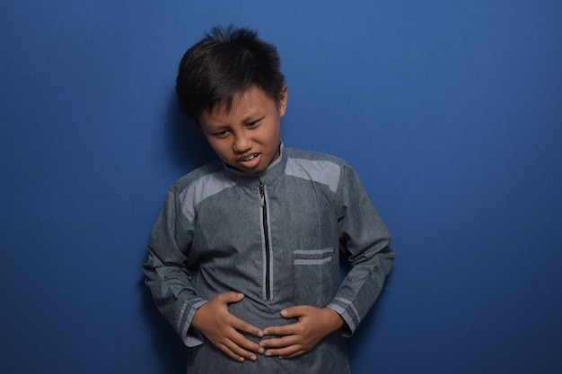 Young asian boy wearing muslim clothes with hand on stomach because indigestion feeling unwell