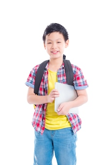 Young asian boy with backpack holding laptop computer and smiles over white background
