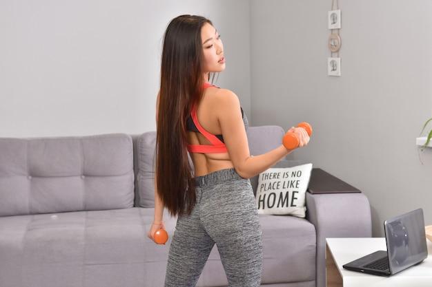 2つのオレンジ色のダンベルでホームワークアウトを作るスポーツウェアの若いアジアのブルネットの女性。
