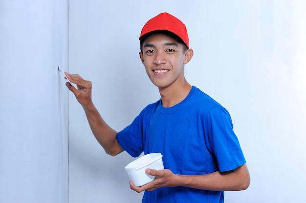 Молодой азиатский человек построителя прикладывая штукатурку шпатлевки на белой стене. от штукатурки стены до отделки стены.