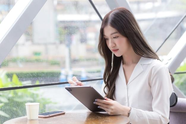 若いアジアのビジネス女性は、彼女が座っている間、彼女の手でタブレットやメモ帳を見ています