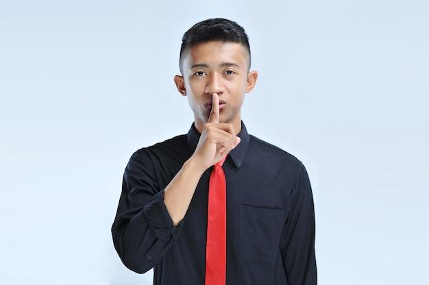 唇に指で静かにすることを求める若いアジアのビジネスマン。孤立した背景上の沈黙と秘密の概念