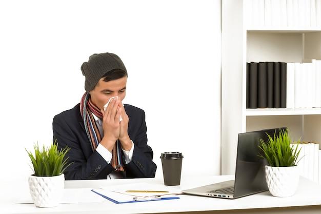 Молодой азиатский деловой человек сморкается, работая на ноутбуке в офисе. - изображение