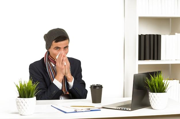 若いアジアのビジネスマンは、オフィスでラップトップに取り組んでいる間、彼の鼻をかむ