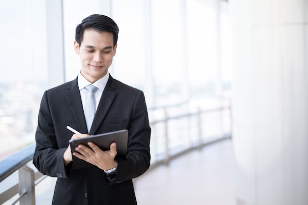 Young asian business man holding a tablet looking screen