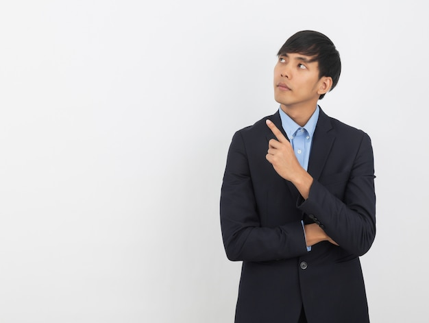 Young asian business man pointing to the side with a finger to present a product or an idea while looking forward isolated