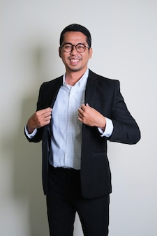 Young asian business man showing proud gesture by touching his suit