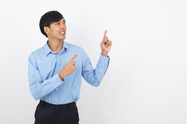 Young asian business man with blue shirt pointing to the side with a finger to present a product or an idea while looking forward smiling isolated on white