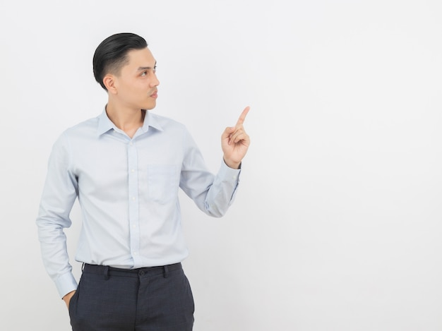 Young asian business man with blue shirt pointing to the side with a finger to present a product