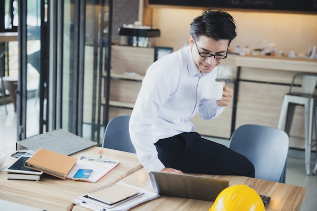 Молодой азиатский деловой человек работает из дома во время отдыха, выпивая чашку кофе и глядя на ноутбук
