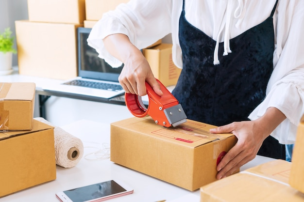 テーブルの上のテープでボックスを密封する若いアジアビジネスオーナー。配送の準備、梱包、オンライン、販売、eコマース、ホームコンセプトでの/からのコンセプト。閉じる。