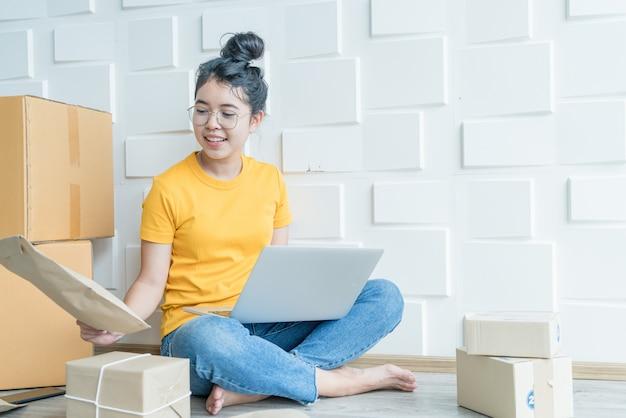 若いアジアのビジネスは、コンピューターを使用して電子メールまたはwebサイトから顧客の注文をチェックし、パッケージを準備するためのオンライン販売者の所有者を立ち上げます