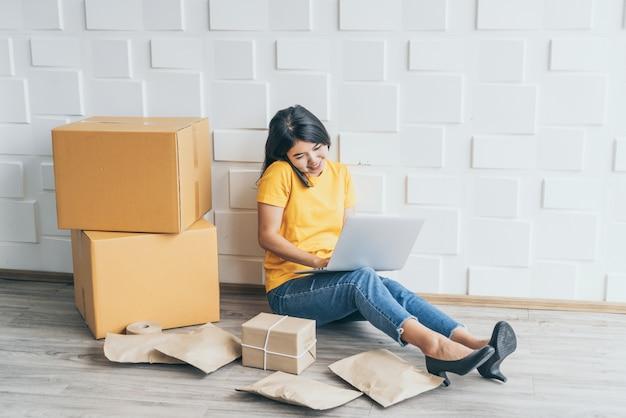 Молодой азиатский бизнесмен запускает онлайн-продавца с помощью компьютера для проверки заказов клиентов по электронной почте или на веб-сайте и подготовки пакетов