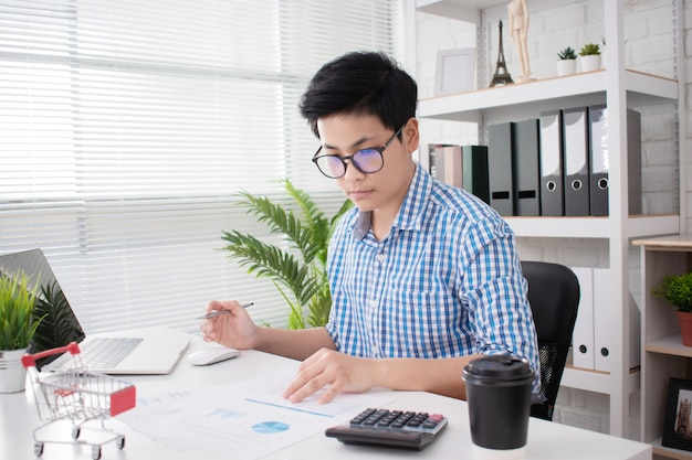 Young asian business wear blue plaid shirts, work seriously in the office.