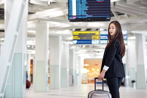 Молодая азиатская бизнес-леди в аэропорту с сумкой тележки, ожидая вылета.