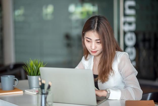 Улыбка молодой азиатской бизнес-леди красивая очаровательная и использование портативного компьютера в современном офисе.