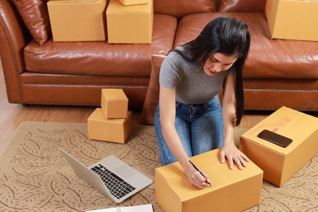 スマートフォンとオンライン購入の買い物注文ボックスで自宅からチェックして働く若いアジアのビジネスウーマン