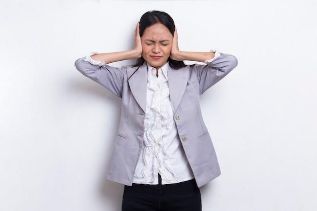 白い背景で隔離の手で両耳を覆う若いアジアのビジネス女性