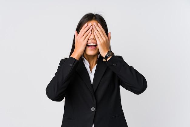 젊은 아시아 비즈니스 여자는 손으로 눈을 다루고, 미소는 놀라움을 광범위하게 기다리고 있습니다.