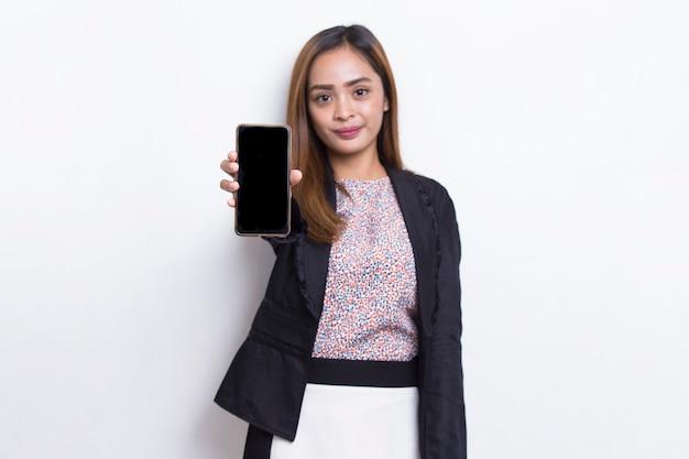 白い背景で隔離の携帯電話を示す若いアジアのビジネス女性
