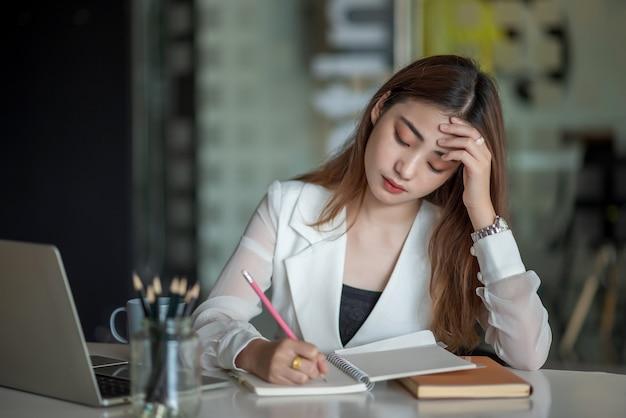 Молодая азиатская бизнес-леди чувствует себя больной и усталой или истощенной от офисной работы.