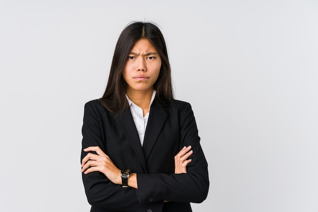 Young asian business woman frowning face in displeasure, keeps arms folded.