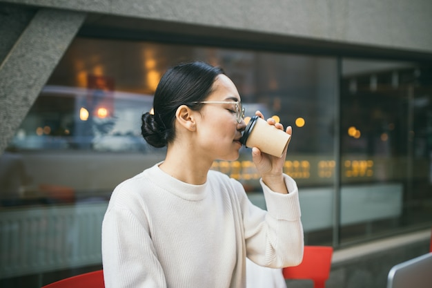 Young asian business woman in glasses is sitting outside a coffee shop, drinking coffee