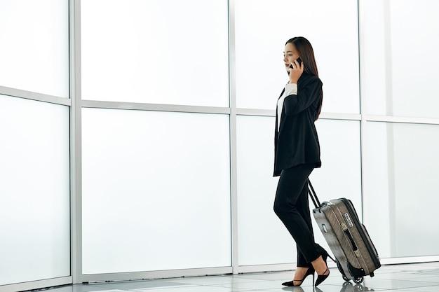 Молодая азиатская бизнес-леди в авиапорте с сумкой багажной тележки, говоря на телефоне и усмехаясь.
