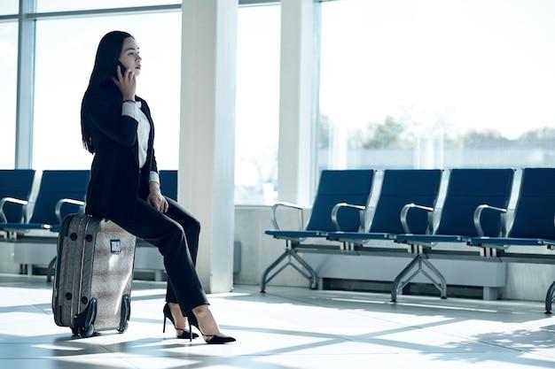 Молодая азиатская бизнес-леди в аэропорту с багажной тележкой, разговаривает по телефону и улыбается.