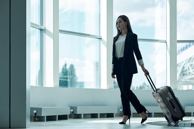 Молодая азиатская бизнес-леди в аэропорту с багажной тележкой в ожидании вылета