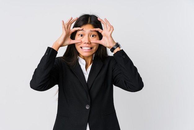 Young asian business woman keeping eyes opened to find a success opportunity.