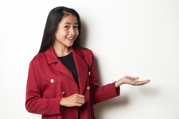 さまざまな方向に指で自信を持って指している笑顔の白い背景の上の若いアジアのビジネス女性。