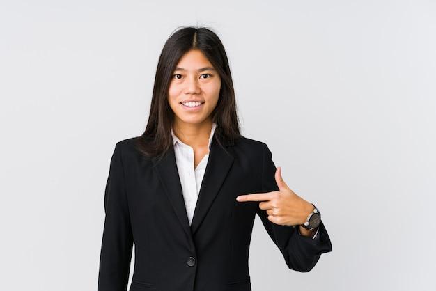 自信を持って自信を持ってシャツコピースペースを手で指している若いアジアビジネス女性人