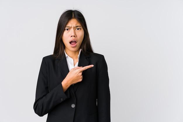 측면을 가리키는 젊은 아시아 비즈니스 우먼