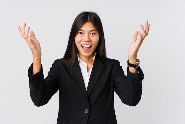 Молодая азиатская бизнес-леди получая приятный сюрприз, возбужденный и поднимая руки.