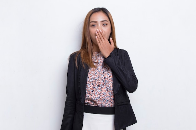 Young asian business woman shocked covering mouth with hands for mistake secret concept