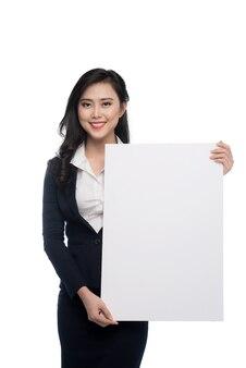 Молодая азиатская бизнес-леди показывая белую доску изолированную на белой предпосылке.