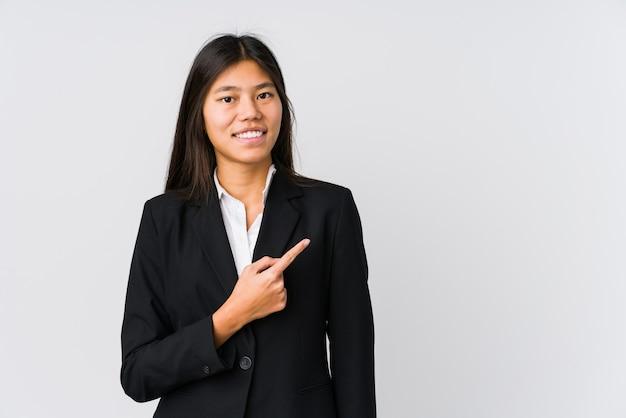 웃 고 옆으로 가리키는, 빈 공간에서 뭔가 보여주는 젊은 아시아 비즈니스 여자.