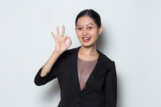 Young asian business woman smiling and making ok sign with hand gesture tumb up