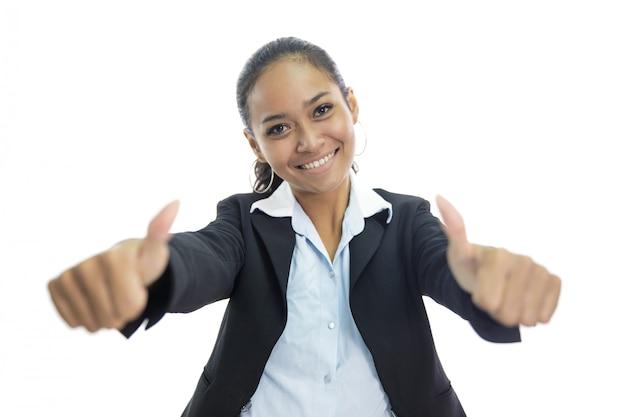 Молодая азиатская бизнес-леди усмехаясь пока дающ 2 большого пальца руки вверх