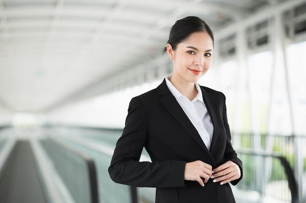 立って笑顔の若いアジアのビジネス女性。