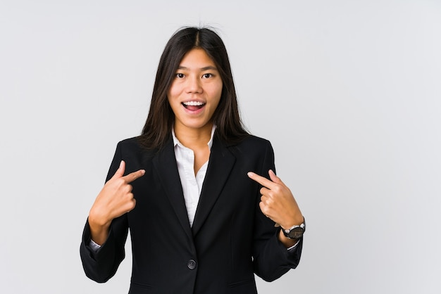 Young asian business woman surprised pointing with finger, smiling broadly.
