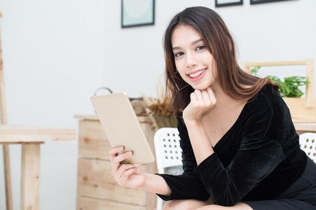 タブレットを使用して若いアジアビジネス女性