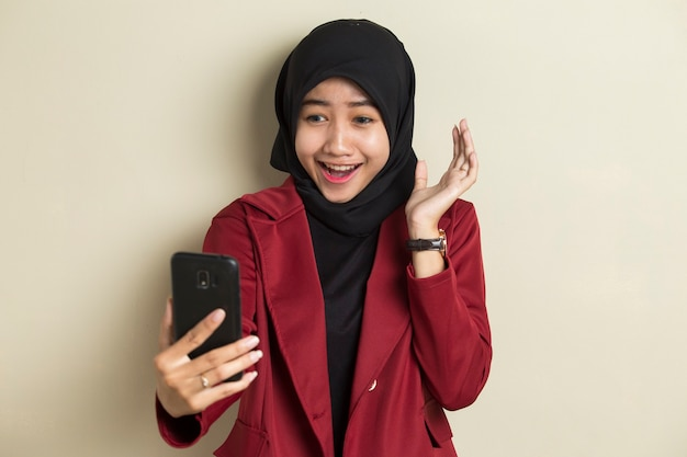 스마트 폰을 사용하여 화상 통화를하는 hijab를 착용하는 젊은 아시아 비즈니스 여성