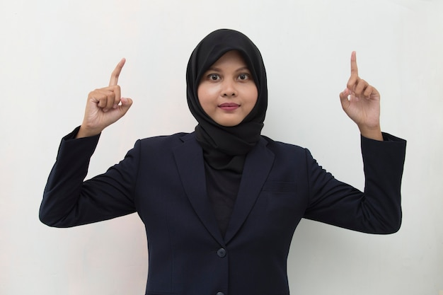 Young asian business woman wearing hijab smiling confident pointing with fingers to different directions copy space for advertisement